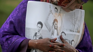 Haqhawo Qaasim holds onto a photo of Guled Ali Omar, who is scheduled to stand trial Monday, while standing in front of the United States Courthouse, Monday, May 9, 2016 in Minneapolis.  (Elizabeth Flores / Star Tribune via AP)