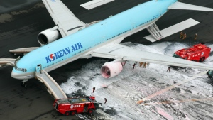 Firefighters gather near an engine of a Korean Air jet following an apparent engine fire on the tarmac at Haneda Airport in Tokyo on Friday, May 27, 2016. (Kyodo News)