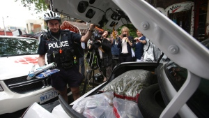 An officer closes the trunk of a police cruiser with confiscated marijuana and other products in front of the Cannawide marijuana dispensary in Toronto on May 26, 2016. (Cole Burston / THE CANADIAN PRESS)
