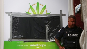 An Toronto Police officer stands outside Cannawide marijuana dispensary during a raid on May 26, 2016. (Cole Burston / THE CANADIAN PRESS)