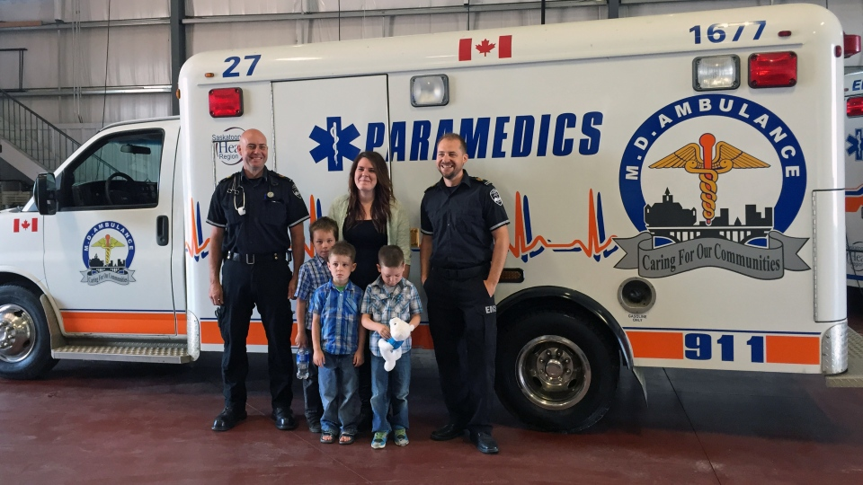 Mother of three Samantha Warren, middle, meets paramedics Tom Barbier, left, and Luc Duval. Barbier and Duval helped her give birth to twins while en route to hospital in Saskatoon five years ago. One of the twins was born in the ambulance. The other was born in hospital. Both boys and their older brother joined their mother in meeting the paramedics Friday. (Taylor Rattray/CTV Saskatoon)