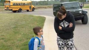 Aleisha McKenzie greets her son Owen at the bus stop near their home