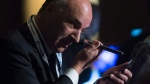 Kevin O'Leary applies his own makeup prior to doing a television interview, at the Conservative Party of Canada convention in Vancouver, Friday, May 27, 2016. (THE CANADIAN PRESS/Jonathan Hayward)