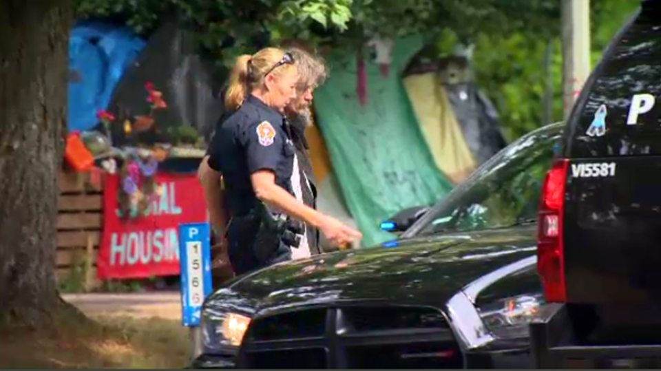 A suspect is taken into Victoria Police custody following an assault on a CTV cameraman at tent city, located at Victoria's courthouse. Fri., May 27, 2016. (CTV Vancouver Island)