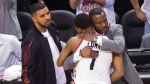 Toronto Raptors guard Kyle Lowry (7) receives a hug from Raptors head coach Dwane Casey, right, as rapper Drake, left, looks on as the Cleveland Cavaliers defeat the Raptors during second half Eastern Conference final NBA playoff basketball action in Toronto on Friday, May 27, 2016. THE CANADIAN PRESS/Nathan Denette