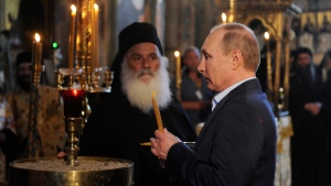 Russian President Vladimir Putin lights a candle as he arrives at the church of the Protaton, dedicated to the Dormition of the Virgin, in Karyes, the administrative center of the all-male Orthodox monastic community of Mount Athos, northern Greece, Saturday, May 28, 2016. (Alexandros Avramidis / Pool Photo via AP)