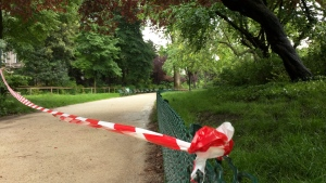 White-and-red tape is strung across a sandy pathway through Park Monceau after a lightning stike, in Paris, Saturday, May 28, 2016. A Paris fire service spokesman says 11 people including eight children have been hit by lightning in a Paris park after a sudden spring storm overtook a child's birthday party. (AP Photo / Raphael Satter)