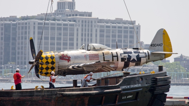 Officials place a plane on the Wall St. Heliport pier after removing it from the Hudson River on May 28, 2016. (Mary Altaffer / AP)