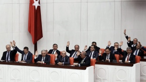 Turkey's new Prime Minister Binali Yildirim, third left, and his ministers raise their hands during a vote of confidence for his cabinet at the parliament in Ankara, Turkey, Sunday, May 29, 2016. The parliament approved the new government. (AP Photo)
