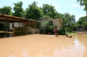 Irene Martinez, who lives near the Brazos River, leaves her flooded home Sunday, May 29, 2016, in Richmond, Texas. Martinez lives there with her two sons, and they are evacuating because the river is expected to rise another several feet. (Jon Shapley/Houston Chronicle via AP)