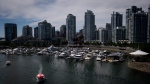 A water taxi decorated with a Canadian flag on the roof travels on False Creek as boats are moored in a marina near Yaletown condo towers in Vancouver, B.C., on July 13, 2014. (THE CANADIAN PRESS/Darryl Dyck)