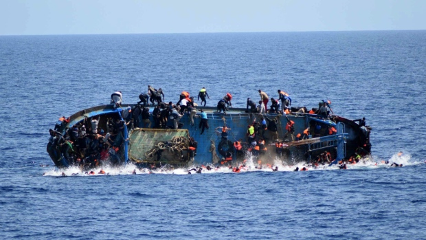 People try to jump in the water right before their boat overturns in the Mediterranean Sea off the Libyan coast on May 25, 2016. (Italian navy via AP)
