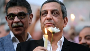In this Tuesday, May 24, 2016 picture, Yahya Qalash, the head of journalists' union, holds a candle during a candlelight vigil for the victims of EgyptAir flight 804 in front of the Journalists' Syndicate in Cairo, Egypt. (AP / Amr Nabil)