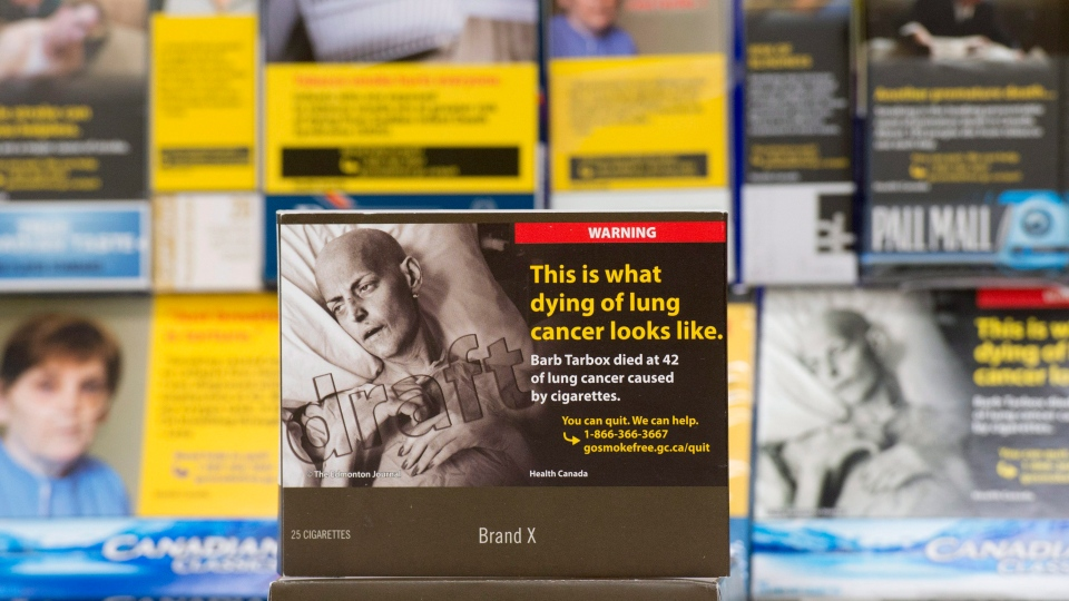 A proposed standardized cigarette package is displayed in front of a variety of cigarette packages available now Friday May 27, 2016 in Ottawa. (THE CANADIAN PRESS/Adrian Wyld)