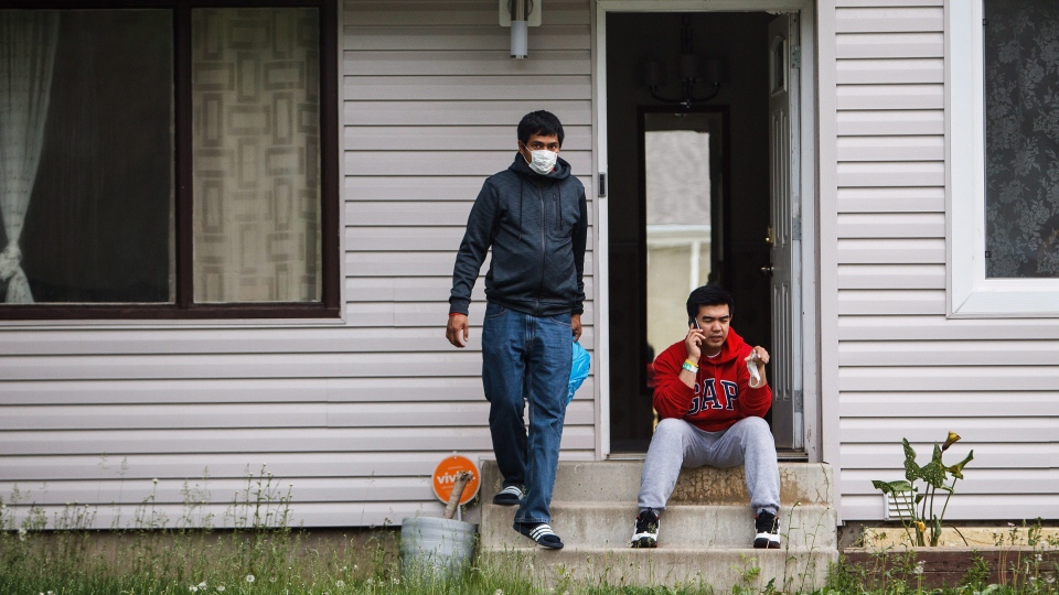 James Turingan, left, and Russell Boston survey the damage to their home as residents re-enter fire-ravaged Fort McMurray, Alta., on Wednesday, June 1, 2016. (THE CANADIAN PRESS/Codie McLachlan)