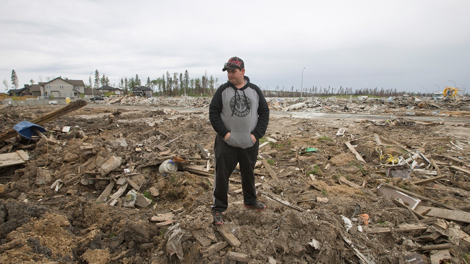 Resident Kenny Gibbons looks through his demolished backyard in the neighbourhood of Timberlea, in Fort McMurray, Alta, on Wednesday, June 1, 2016. (Jason Franson / THE CANADIAN PRESS)