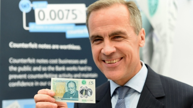Governor of the Bank of England, Mark Carney, unveils the full design of the new polymer £5 note featuring Sir Winston Churchill on June 2, 2016. (Joe Giddens/PA via AP)