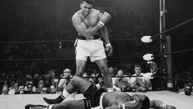 In this May 25, 1965 file photo, Heavyweight champion Muhammad Ali stands over fallen challenger Sonny Liston, shouting and gesturing shortly after dropping Liston with a short hard right to the jaw in Lewiston, Maine (AP / John Rooney)