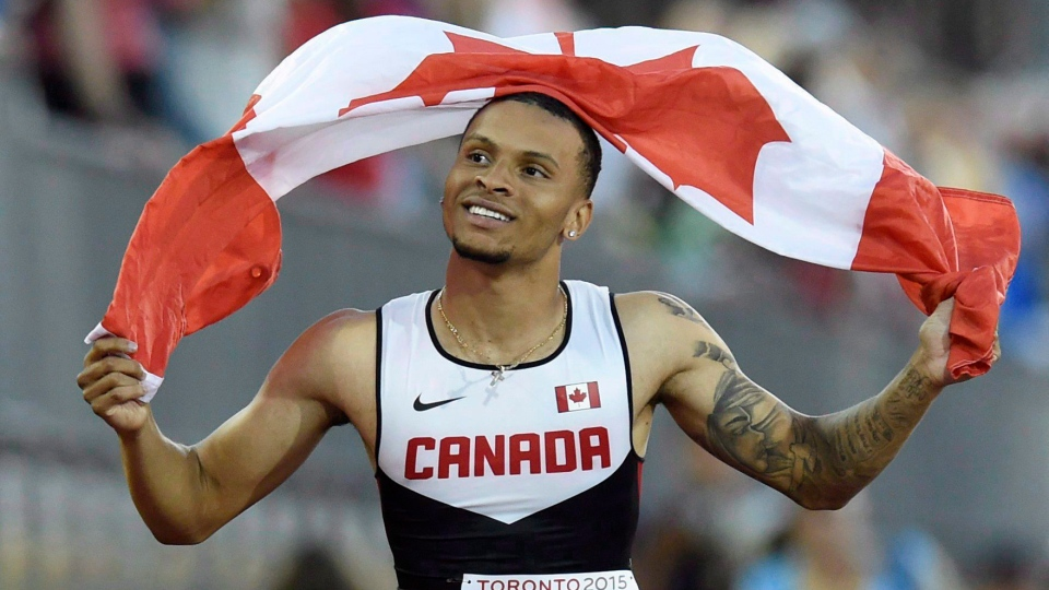 In this file photo, Andre De Grasse, of Canada, holds a flag after he wins the gold medal in the men's 100m final during the athletics competition at the 2015 Pan Am Games in Toronto on Wednesday, July 22, 2015. (Frank Gunn/The Canadian Press)
