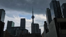 A patch of blue sky is visible amid storm clouds behind the CN Tower in downtown Toronto Sunday June 5, 2016. (Joshua Freeman /CP24)