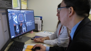 Dr. Ronald C. Chen consults with colleague Misty Lehman-Davis on a cancer patient's scans at the UNC Lineberger Comprehensive Cancer Center in Chapel Hill, N.C., on May 27, 2016. (Allen G. Breed / AP)