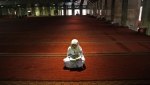 A Muslim woman reads the Quran following noon prayers on the first day of the holy fasting month of Ramadan at Istiqlal Mosque in Jakarta, Indonesia, Monday, June 6, 2016. (AP Photo/Tatan Syuflana)
