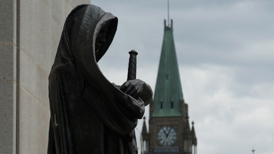 The Peace tower on Parliament Hill is seen behind the justice statue outside the Supreme Court of Canada in Ottawa, Monday, June 6, 2016. (Adrian Wyld / THE CANADIAN PRESS)