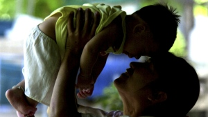 An HIV-positive mother plays with her son, who did not contract the virus from her, in Phetchaburi province, south of Bangkok on June 17, 2004. (AP / Sakchai Lalit)