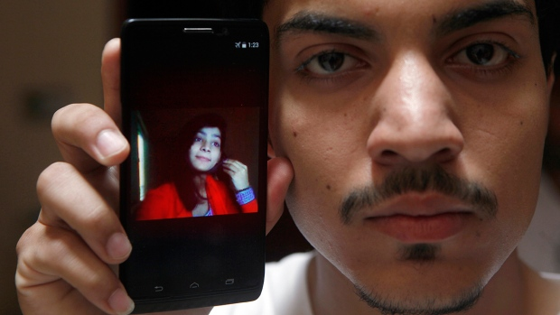 Hassan Khan shows the picture of his wife Zeenat Rafiq, who was burned alive, allegedly by her mother, on a mobile phone at his home in Lahore, Pakistan Wednesday, June 8, 2016. (AP / K.M. Chaudary)