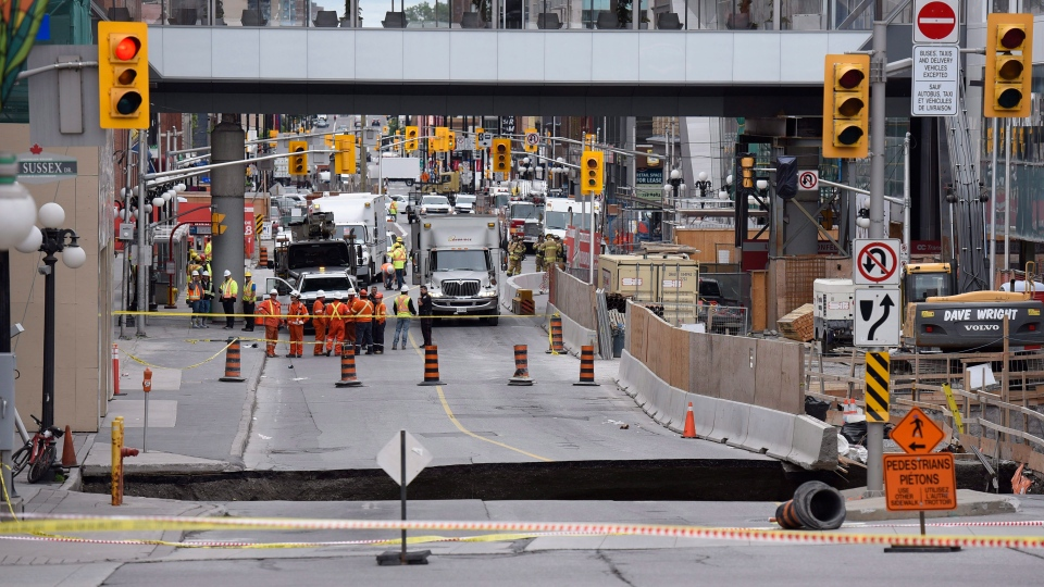 A large sinkhole that formed on Rideau Street next to the Rideau Centre mall is seen on Wednesday, June 8, 2016 in Ottawa. (THE CANADIAN PRESS/Justin Tang)