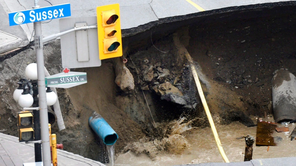 Water splashes as soil collapses into a large sinkhole that formed on Rideau Street next to the Rideau Centre Mall on Wednesday, June 8, 2016 in Ottawa. (THE CANADIAN PRESS/Justin Tang)
