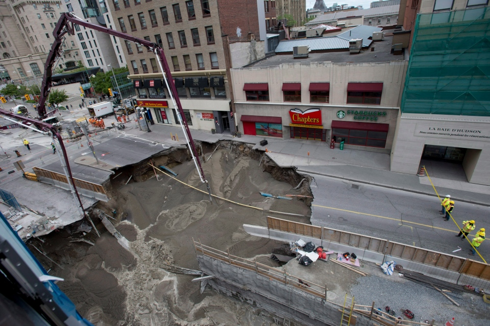 Workers look on as boom concrete pumps fill a large sinkhole that formed Wednesday morning on Rideau Street, Thursday, June 9, 2016 in Ottawa. THE CANADIAN PRESS/Justin Tang