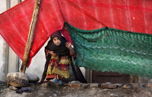 In this Sunday, Nov. 29, 2015 photo, an internally displaced girl peeks from a tent after her family left their village in Rodat district of Jalalabad east of Kabul, Afghanistan. (AP / Rahmat Gul)
