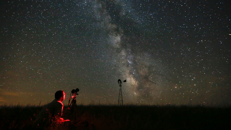 In this Wednesday, July 23, 2014 file photo, Lane Hickenbottom photographs the night sky in a pasture near Callaway, Neb. (Travis Heying/The Wichita Eagle via AP)