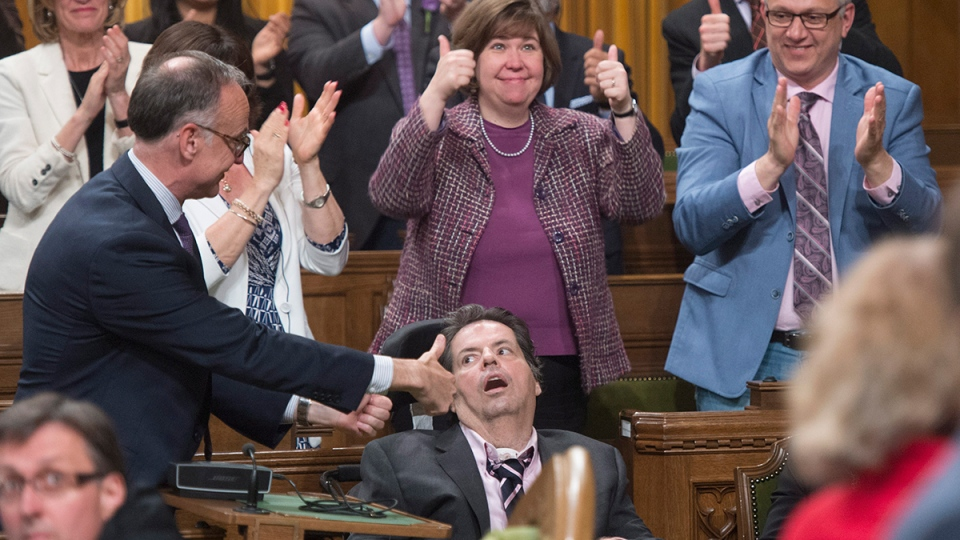 Members of Parliament applaud and give the thumbs up sign to Ottawa-Vanier MP Mauril Belanger as his private members bill on changing the Canadian anthem is debated in the House of Commons, Friday, June 10, 2016 in Ottawa. (Adrian Wyld / THE CANADIAN PRESS)