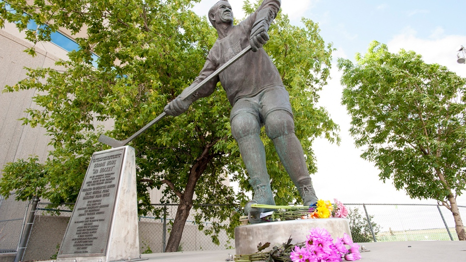 Flowers left at a statue of Gordie Howe at the Sasktel Centre in Saskatoon, Friday, June 10, 2016. (Liam Richards / THE CANADIAN PRESS)