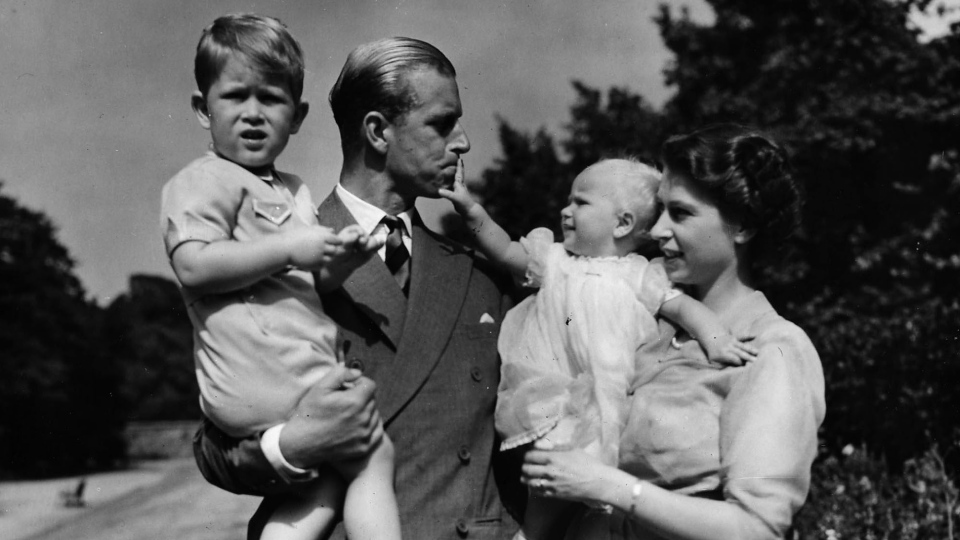 In this Aug. 1951 file photo, Princess Elizabeth stands with her husband Prince Philip, the Duke of Edinburgh, and their children Prince Charles and Princess Anne at the couple's London residence at Clarence House. (AP Photo / Eddie Worth, file)