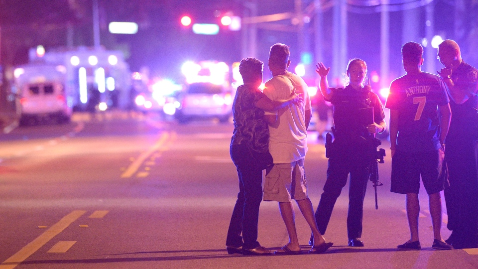 Orlando Police officers direct family members away from a multiple shooting at a nightclub in Orlando, Fla., Sunday, June 12, 2016. (AP / Phelan M. Ebenhack)