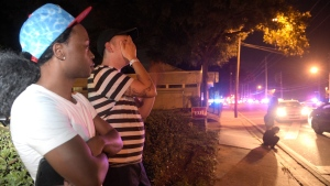 Jermaine Towns, left, and Brandon Shuford wait down the street from a multiple shooting at a nightclub in Orlando, Fla., Sunday, June 12, 2016. (AP Photo / Phelan M. Ebenhack)