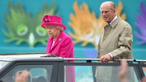 Queen Elizabeth II and the Duke of Edinburgh arrive at the Patron's Lunch in The Mall, central London in honour of the her 90th birthday, in an open topped Range Rover, Sunday June 12, 2016. The Queen's grandson Peter Phillips has masterminded the street party for 10,000 people, to mark the monarch's patronage of more than 600 charities and organisations. (Dominic Lipinski / AP)