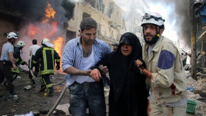 In this photo taken on June 8, 2016 provided by the Syrian Civil Defense Directorate in Liberated Province of Aleppo, which has been authenticated based on its contents and other AP reporting, shows Syrian civil defense workers, right, helps an injured woman after warplanes attacked a street, in Aleppo, Syria.. (Civil Defense Directorate in Liberated Province of Aleppo via AP)