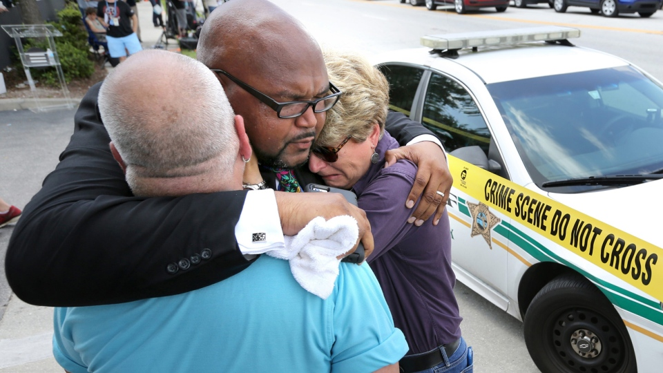Kelvin Cobaris, a local clergyman, consoles Orlando city commissioner Patty Sheehan, right, and Terry DeCarlo, an Orlando gay-rights advocate, as they arrive on the scene near where a mass shooting occcured in Orlando, Fla., Sunday, June 12, 2016. (Joe Burbank/Orlando Sentinel via AP)