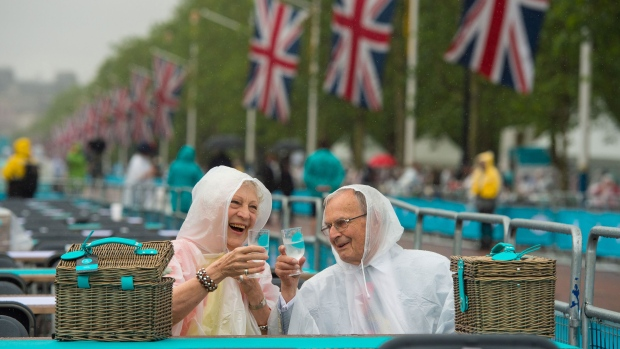 Wearing plastic rain ponchos, people sit with their specially prepared picnic hampers, in The Mall, central London, ahead for the Patron's Lunch in honour of the Queen's 90th birthday, Sunday June 12, 2016. The Queen's grandson Peter Phillips has masterminded the street party for 10,000 people, Sunday, to mark the monarch's patronage of more than 600 charities and organizations. (Dominic Lipinski / PA via AP)