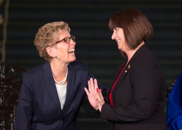 Ontario Premier Kathleen Wynne laughs with Marie-France Lalonde, Minister of Government and Consumer Services and Minister Responsible for Francophone Affairs after her swearing in at Queen's Park in Toronto on Monday, June 13, 2016. (Peter Power / THE CANADIAN PRESS)