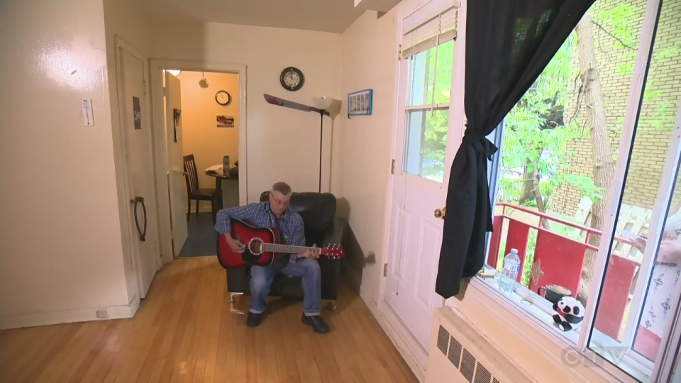 Roger Flowers, who was homeless for 30 years, plays guitar in his apartment