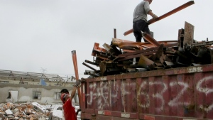 Scrap collectors load materials into a truck on the site of demolished factories in Zhoupu Township in Pudong district of Shanghai to make way for a new Disney theme park on June 7, 2016. (AP / Paul Traynor)