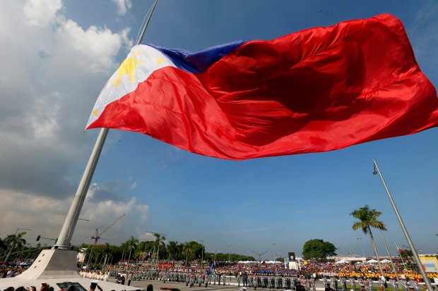 A giant Philippine flag is raised during a ceremony to celebrate the 118th Philippine Independence Day rites at the Rizal Park Sunday, June 12, 2016 in Manila, Philippines. (AP Photo/Bullit Marquez)