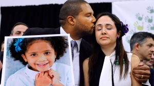 In this Jan. 14, 2013 file photo, Jimmy Greene, left, kisses his wife Nelba Marquez-Greene as he holds a portrait of their daughter, Sandy Hook School shooting victim Ana Marquez-Greene, at a news conference in Newtown, Conn. (AP / Jessica Hill, File)