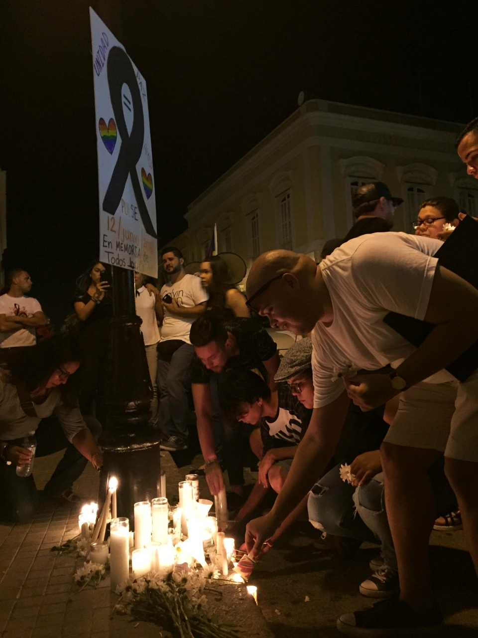 People light candles in Ponce, Puerto Rico, Monday, June 13, 2016, during a vigil for the victims of Sunday's Orlando shootings at a gay nightclub in Florida. (Danica Coto/AP Photo)
