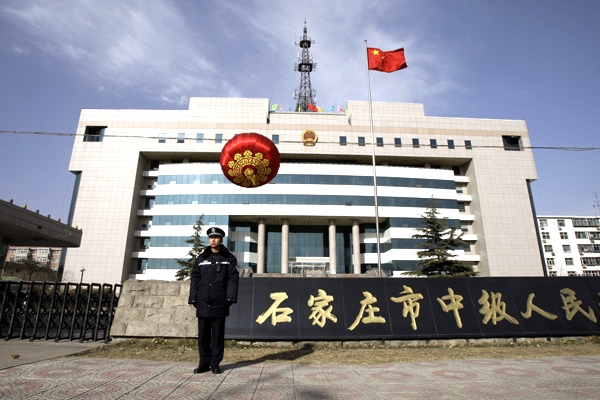 A police officer stands guard outside the Intermediate People's Court in Shijiazhuang, in China's Hebei Thursday Jan. 22, 2009. (AP / Greg Baker)